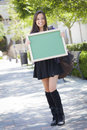 Excited mixed race female student holding blank chalkboard portrait of an attractive and carrying backpack on school campus Royalty Free Stock Photography