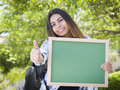 Excited mixed race female student holding blank chalkboard portrait of an attractive and carrying backpack on school campus Stock Photography
