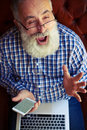 Excited old man with laptop and smartphone Royalty Free Stock Photo