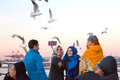 Excited People feeding Sea Gulls chasing Ferry Boat Royalty Free Stock Photo