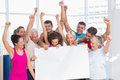 Excited people holding blank billboard at gym fit against window Royalty Free Stock Images
