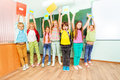 Excited schoolchildren hold textbooks up with arms group of in the air stand close together near blackboard in school Royalty Free Stock Photo