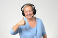 Excited senior woman listening to music on a set of stereo headphones smiling with enjoyment and giving thumb up gesture over grey Royalty Free Stock Photos
