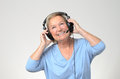 Excited senior woman listening to music on a set of stereo headphones smiling with enjoyment and looking up the sky over grey Stock Images