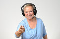 Excited senior woman listening to music on a set of stereo headphones smiling with enjoyment and pointing at the camera over grey Royalty Free Stock Photos