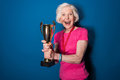 Excited senior woman in sportswear holding trophy
