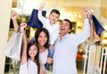 Excited shopping family arms up holding bags Royalty Free Stock Photo
