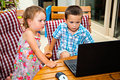 Excited siblings with laptop computer serious children at home Stock Image