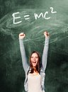 Excited student woman is standing with chalk board behind her Stock Photo