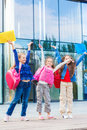 Excited students with backpacks beside school building Stock Photo