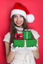 Excited teenage girl holding christmas gift boxes pretty young caucasian with santa hat smiling posing against red background Stock Photo