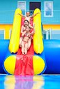 Excited teenage kids down on water slide the Royalty Free Stock Photography