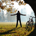 Excited woman cyclist standing in a park Royalty Free Stock Photos