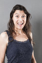 Excited woman expressing amazement or surprise concept young with long fine hair mouth and eyes wide opened grey background studio Stock Photo