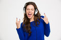 Excited woman in headphones listening to music and gesturing rock pretty young showing gesture over white background Royalty Free Stock Image