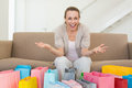 Excited woman looking at camera with many shopping bags home in the living room Royalty Free Stock Image