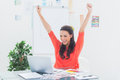 Excited woman raising her arms while working on her laptop in office Stock Photography