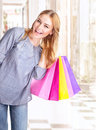 Excited woman with shopping bags in the mall buying presents happy consumer spending money in fashionable boutique Stock Photos