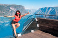 Excited woman tourist at stegastein viewpoint in a summer sunny day showing thumb up gesture flam norway Stock Photos