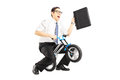 Excited young businessman with leather suitcase riding a small b bicycle isolated against white background Royalty Free Stock Photo
