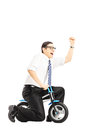 Excited young businessperson riding a small bicycle and gesturin gesturing happiness with his hand isolated on white background Royalty Free Stock Image