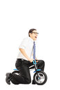 Excited young businessperson riding a small bicycle isolated against white background Stock Photos