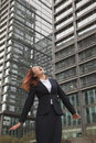 Excited young businesswoman looking up with wind blowing in her hair Royalty Free Stock Photo