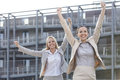 Excited young businesswomen with arms raised against office building Stock Photography