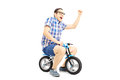Excited young male riding a small bicycle and gesturing happines happiness isolated against white background Royalty Free Stock Photo