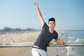 Excited young man with hand raised at the beach portrait of an Stock Image