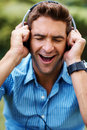 Excited young man listening to music on headphone Stock Photography