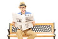Excited young man reading a newspaper seated on bench isolated white background Royalty Free Stock Images