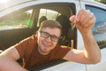 Excited young man showing a car key inside his new vehicle Royalty Free Stock Photo