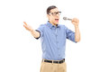Excited young man singing on microphone isolated white background Royalty Free Stock Photos
