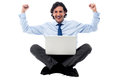 Excited young professional with laptop businessman sitting on floor Royalty Free Stock Image