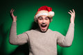 Excited young santa man is winning and screaming of joy on green background Royalty Free Stock Images