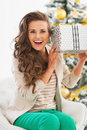 Excited young woman with christmas shaking present box in front of tree tree Royalty Free Stock Images