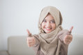 Excited young woman with hijab smiling to camera and showing thu