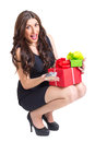 Excited young woman holding presents pretty caucasian brunette wearing little black dress and black shoes with high heels isolated Royalty Free Stock Photos