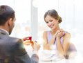 Excited young woman looking at boyfriend with ring restaurant couple and holiday concept women engagement restaurant Royalty Free Stock Image