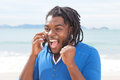 Exciting african american guy with dreadlocks at phone outdoors beach ocean and sky in the background Stock Images