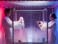 Exciting chemistry in sterile chamber two scientists a men and a woman examining results of a chemical reaction a labeled as bio Royalty Free Stock Photography