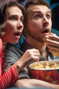 Exciting movie close up of shocked young couple eating popcorn and drinking soda while watching at the cinema Royalty Free Stock Photos