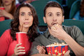 Exciting movie shocked young couple eating popcorn and drinking soda while watching at the cinema Royalty Free Stock Photography