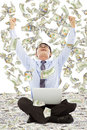 Exciting young businessman raise hands with money background Stock Images