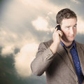 Executive business man on cell phone outdoors standing against a cloud background Stock Images