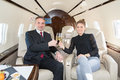 Executive business team in a corporate jet drinking a glass of c traveling and discussing presentation travel Royalty Free Stock Photo