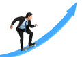 Executive on skateboard going up the rising chart isolated over white background Stock Photos
