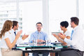 Executives clapping around conference table business in a bright office Stock Image