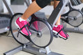 Exercise bike with spinning wheels woman biking excising in fitness center closeup of pedals professional fitness center equipment Stock Image